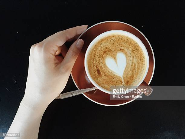 Cropped Image Of Woman With Cappuccino Served On Table