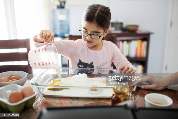 Cropped image of woman with daughter preparing food at home