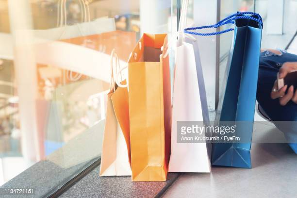 Cropped Image Of Woman With Shopping Bags Sitting On Floor In Mall