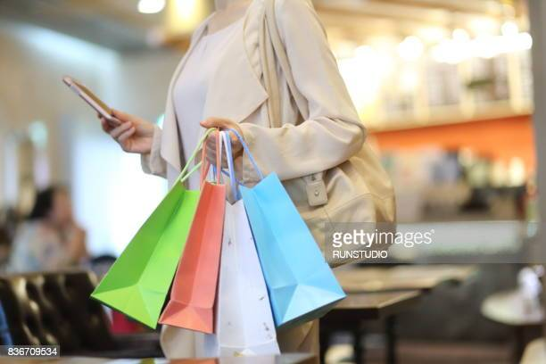 cropped image of woman with shopping bags using a mobile phone - shopping mall stockfoto's en -beelden