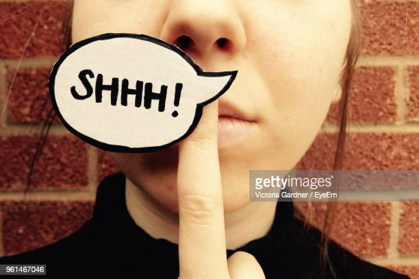 cropped image of woman with text on speech bubble against brick wall - quotation text stock photos and pictures