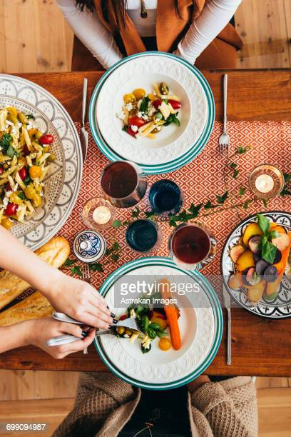Cropped image of womans hands serving food to friends at table