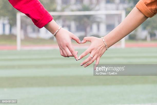 Cropped Image Of Women Making Heart Shape On Playing Field