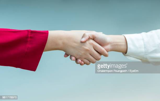 cropped image of women shaking hands against blue background - hand shaking hands stock pictures, royalty-free photos & images