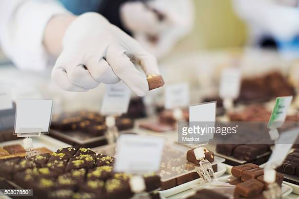 cropped image of worker holding sweet food at display cabinet at cafe - chocolate factory stock photos and pictures