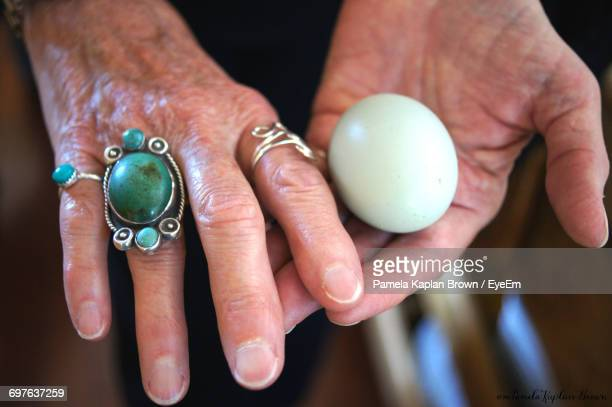 Cropped Image Of Wrinkled Hand Wearing Green Ring Holding White Stone