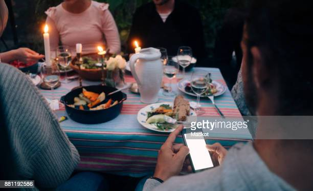 Cropped image of young man using smart phone while having dinner with friends