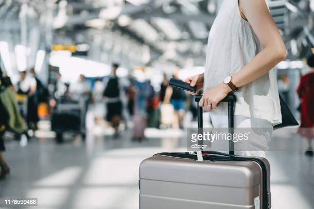 cropped image of young woman holding passport and suitcase walking in the international airport hall - baggage claim stock pictures, royalty-free photos & images