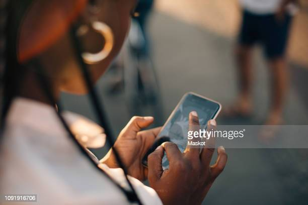 cropped image of young woman using smart phone while standing on street in city - over the shoulder view stock pictures, royalty-free photos & images