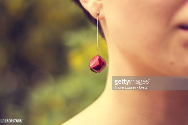 cropped image of young woman wearing red earring - earring stock pictures, royalty-free photos & images