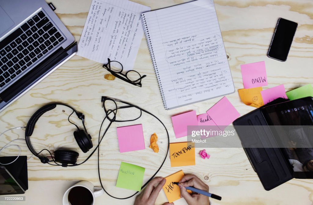 Cropped image of young woman writing in adhesive note at wooden desk : Stock Photo