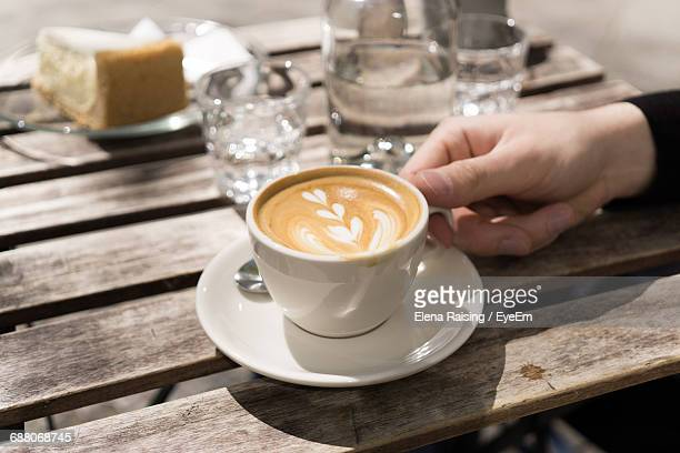 Cropped Image Person Holding Cappuccino On Wooden Table
