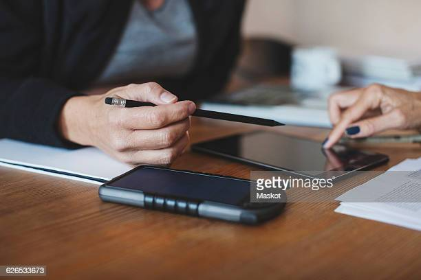Cropped image product designers using digital tablet at home office