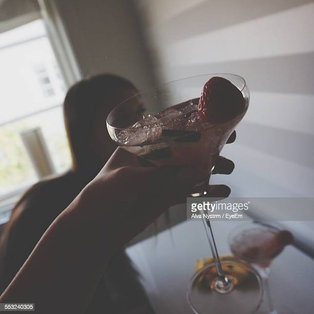 cropped image woman holding cocktail at home - incidental people stock pictures, royalty-free photos & images