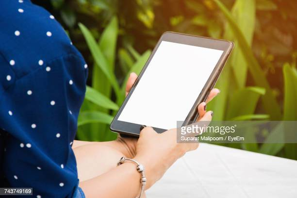 Cropped Image Woman Using Digital Tablet While Siting At Table