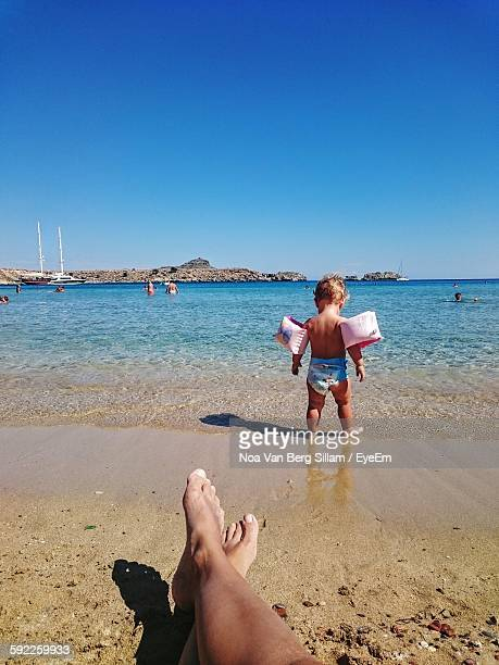 Cropped Legs Of Man In Front Of Child Wearing Water Wings By Sea Against Sky
