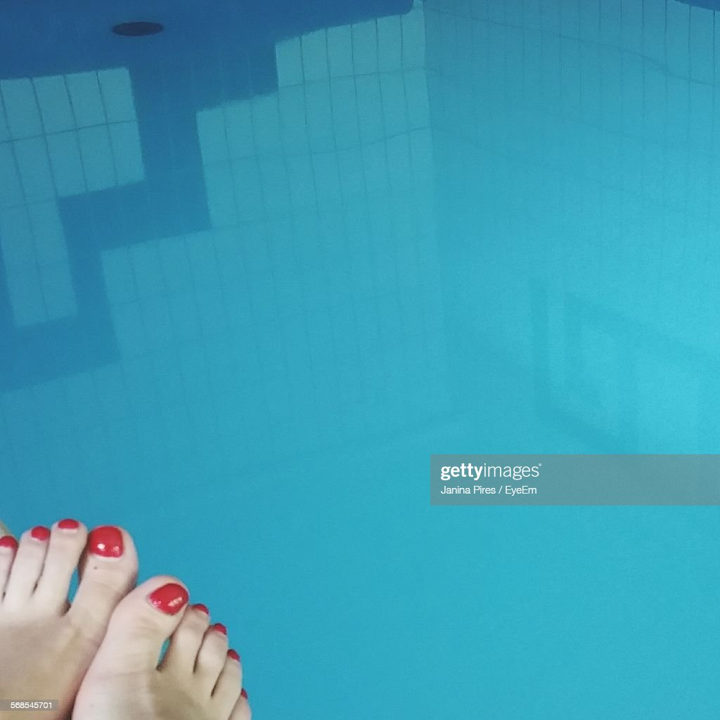 Cropped Legs With Red Nail Polish Relaxing Over Swimming Pool : Stock Photo
