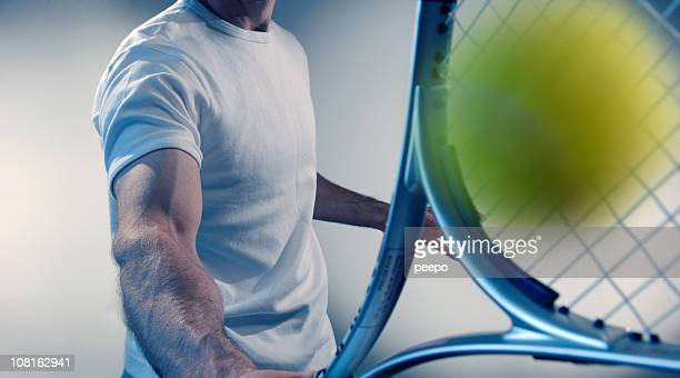 Cropped, Male tennis player hitting ball