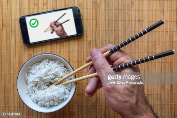cropped man hand learning from youtube how to holding chopsticks - tutorial stock pictures, royalty-free photos & images