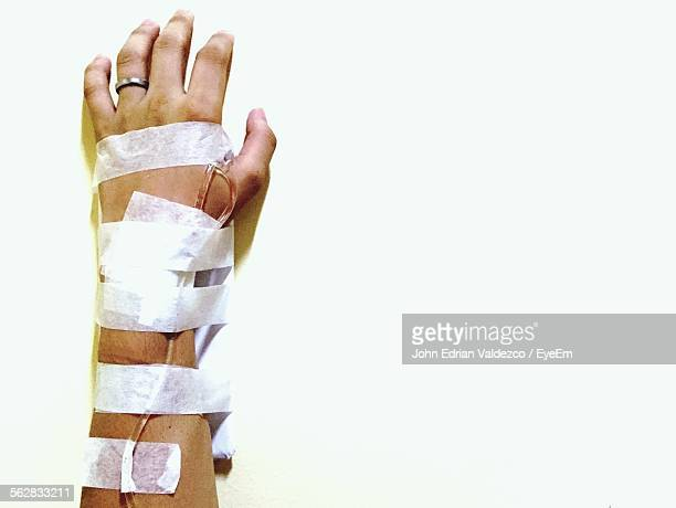 cropped man hand with iv drip pipe against white wall - iv going into an arm stock photos and pictures