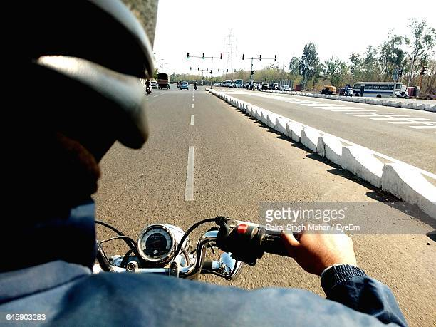 Cropped Man Riding Motorcycle On Road