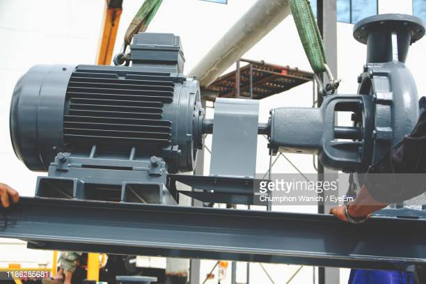 cropped man standing by machinery - water pump stock pictures, royalty-free photos & images