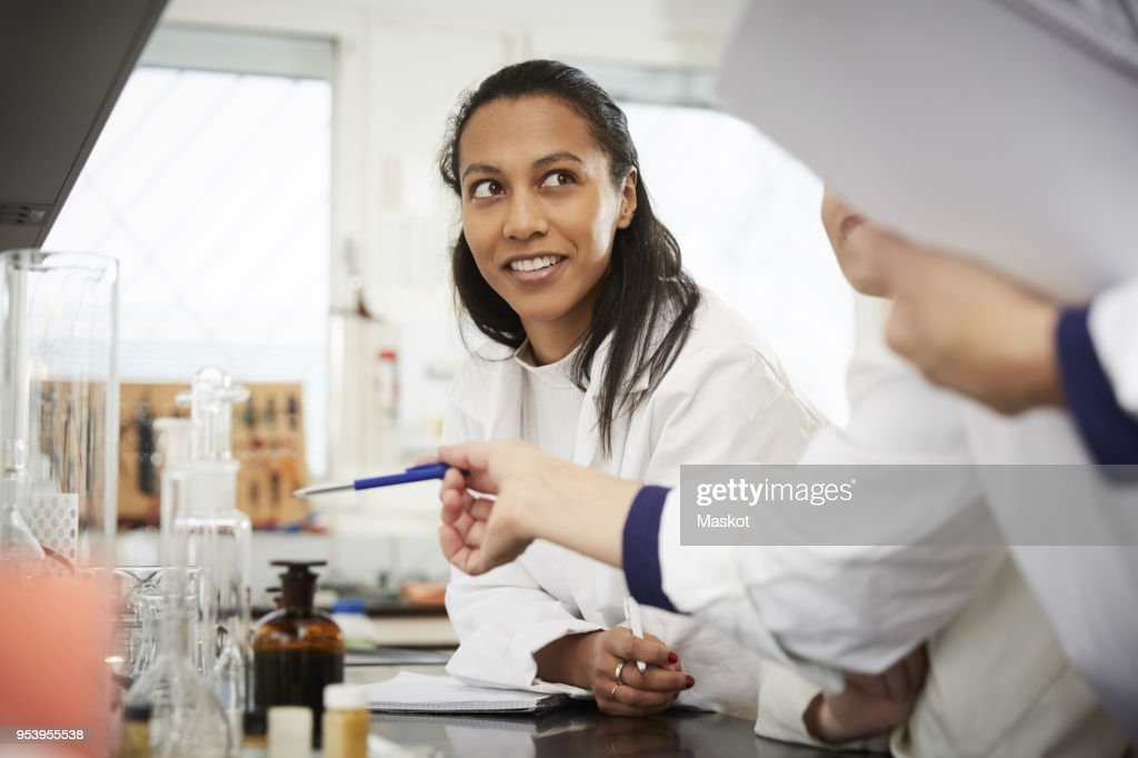 Cropped mature female chemistry teacher explaining to young students in laboratory : Stock Photo