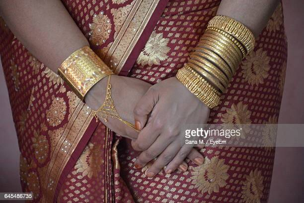 Cropped Mid Section Of A Woman Wearing Bangles