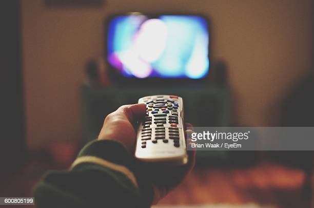 cropped of person holding remote control against television set at home - afstandsbediening stockfoto's en -beelden
