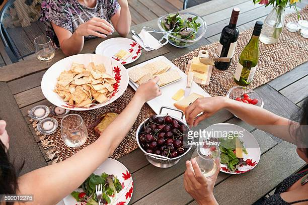Cropped overhead view of female friends eating lunch on patio