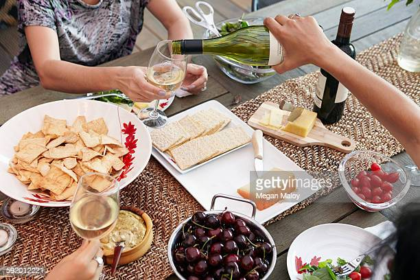 Cropped overhead view of female friends pouring wine at lunch table