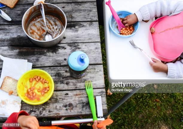 Cropped overhead view of two toddlers eating baked beans on camping site