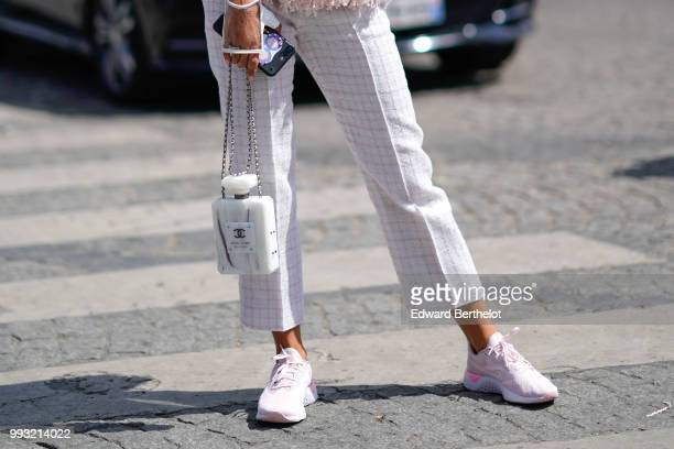 Cropped pants, white sneakers shoes a white Chanel bag in the form of a fragrance bottle , outside Chanel, during Paris Fashion Week Haute Couture...