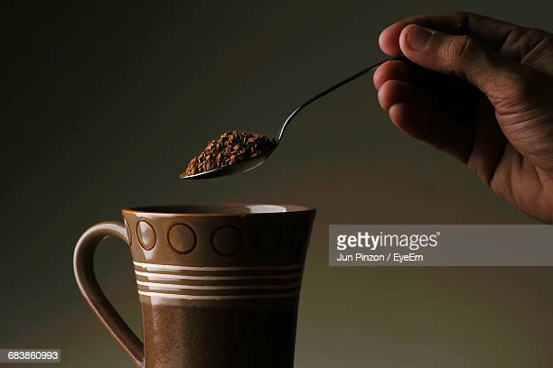 cropped person holding spoon of ground coffee against gray background - ground coffee fotografías e imágenes de stock