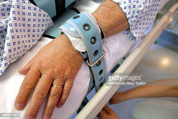 cropped person lying in hospital bed - tied to bed stock pictures, royalty-free photos & images