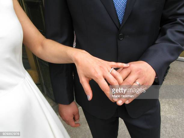 cropped photo of a bride and groom showing their wedding bands. - manos entrelazadas fotografías e imágenes de stock