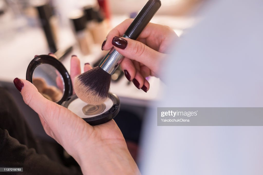 Cropped photo of female arms with powder and brush in saloon : Stock Photo