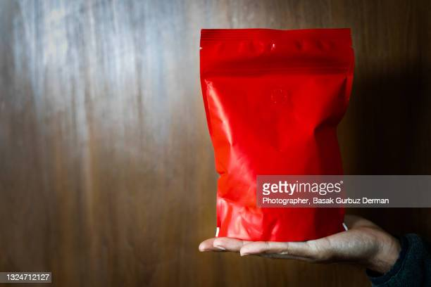 cropped photograph of a man holding a re-sealable zipper bag - sachet stock pictures, royalty-free photos & images
