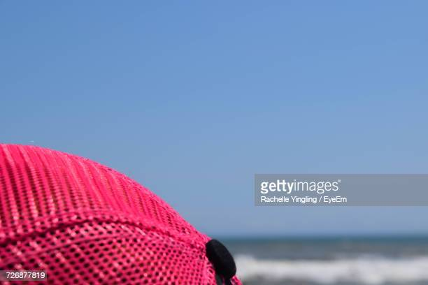 Cropped Pink Baseball Cap Against Clear Blue Sky