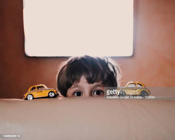 cropped portrait of boy with toy cars on sofa - toy car stock pictures, royalty-free photos & images