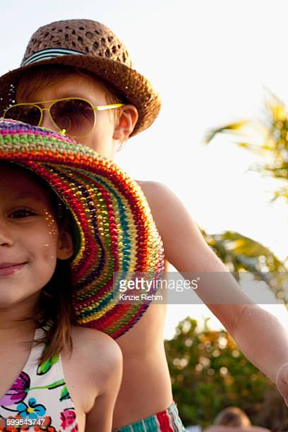Cropped portrait of girl and brother wearing sunhats on beach, Sanibel, Florida, USA