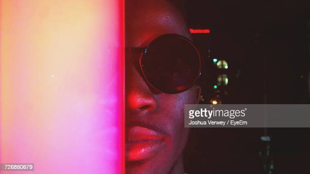 Cropped Portrait Of Man Wearing Sunglasses While Standing By Illuminated Neon Lights