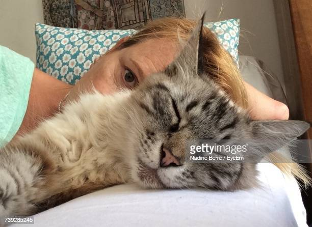 Cropped Portrait Of Woman Sitting By Cat Sleeping On Sofa