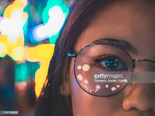 cropped portrait of woman wearing eyeglasses with reflection in illuminated city at night - eyesight stock photos and pictures
