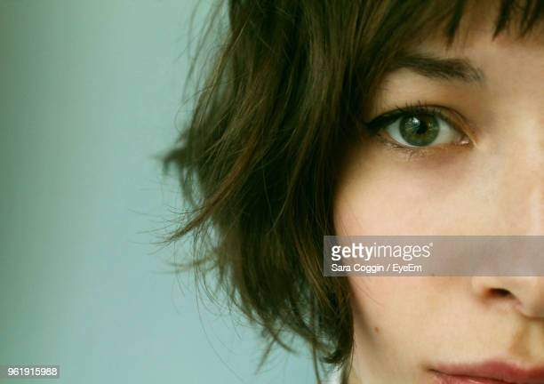 cropped portrait of young woman against green background - eyelid stock photos and pictures