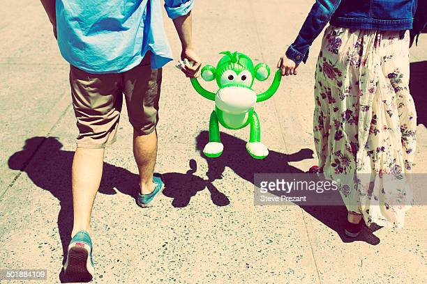 cropped rear view of couple holding hands with inflatable monkey - monkey man stock pictures, royalty-free photos & images