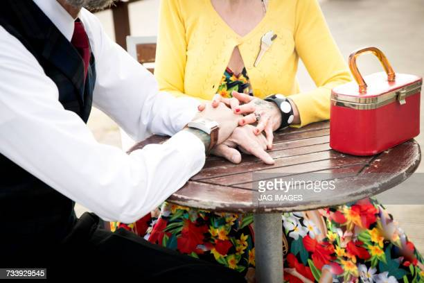 Cropped shot of 1950s vintage style couple holding hands at table