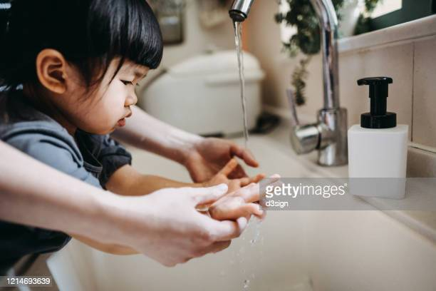 cropped shot of a mother and little daughter maintaining hands hygiene and washing their hands with soap together in the sink - badkamer huis stockfoto's en -beelden