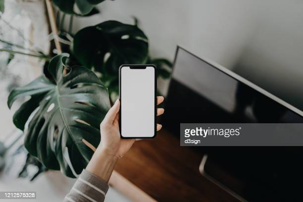 cropped shot of a woman's hand using smartphone in the living room at home - mano humana fotografías e imágenes de stock