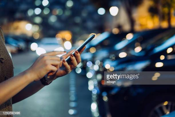 cropped shot of a woman's hand using smartphone while walking to her car in car park in city at night - woman hurry stockfoto's en -beelden